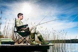 Man fishing at lake sitting on jetty close to the water
