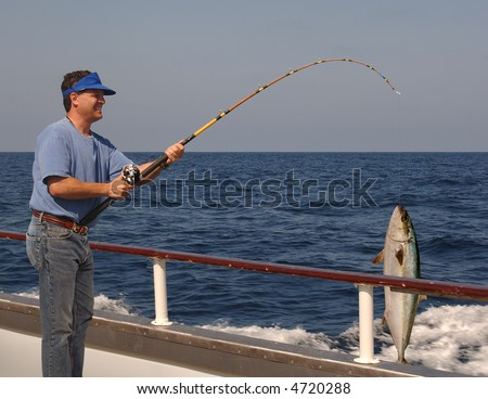 Man fishing from the edge of a moving boat with a live yellow tail tuna hanging from the fishing line #4720288
