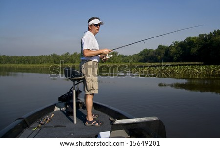 Man fishing in a river off the end of his bass boat.