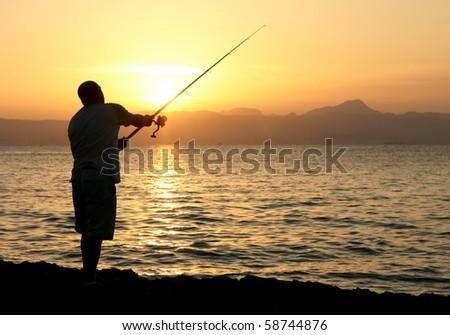Man fishing in last rays of sunlight on sea shore
