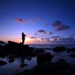 Man fishing in last rays of sunlight on sea shore,Thailand