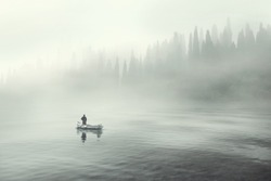 Man fishing on a boat in a mystic foggy lake