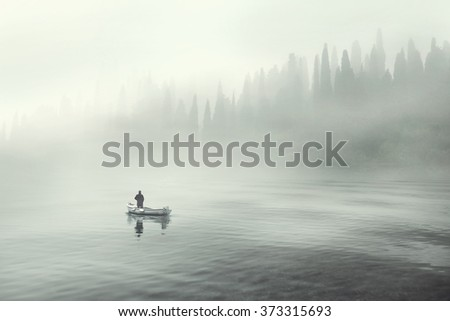 Man fishing on a boat in a mystic foggy lake
