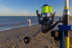 man fishing on beach and close up of fishing rod and reel