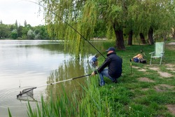 Man fishing with rod on the lake in spring