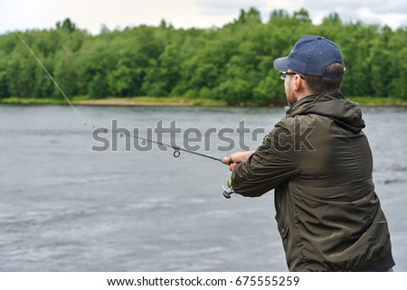 Man fishing with spinning rod in a rapid river. #675555259