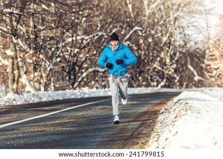Man fitness concept - running and jogging, outdoor training in snow on a cold sunny day