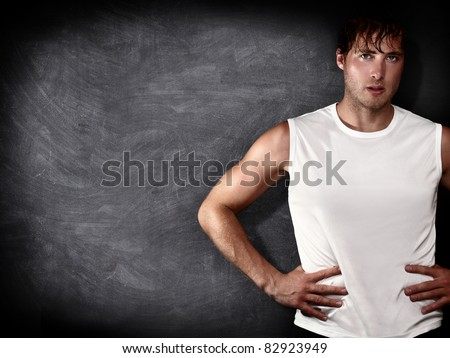 Man fitness model in front of empty blackboard / chalkboard with copy space for text, message or design. Caucasian male fit model on black background.