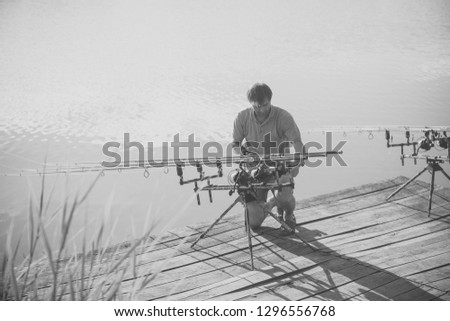 Man fix fishing equipment on wooden pier. Fisherman with spinning rods, reels at freshwater. Summer vacation, adventure, activity. Fishing, angling, hobby, sport, recreation #1296556768