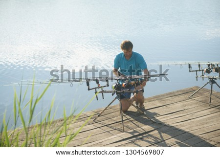 Man fix fishing equipment on wooden pier. Fisherman with spinning rods, reels at freshwater. Summer vacation, adventure, activity. Fishing, angling, hobby, sport, recreation #1304569807