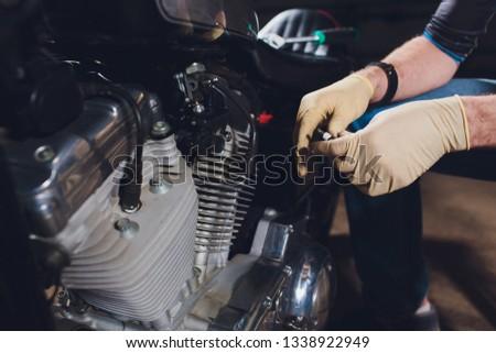 Man fixing bike. Confident young man repairing motorcycle near his garage. #1338922949