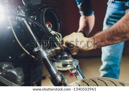 Man fixing bike. Confident young man repairing motorcycle near his garage. replacement lamp in the headlamp #1340503961