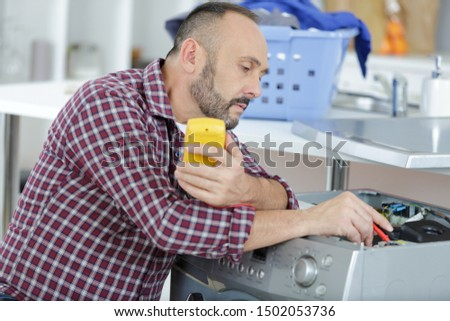 man fixing domestic washing machine