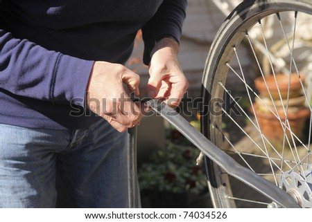 Man fixing flat tire of bike