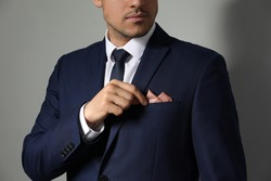 Man fixing handkerchief in breast pocket of his suit on light grey background, closeup