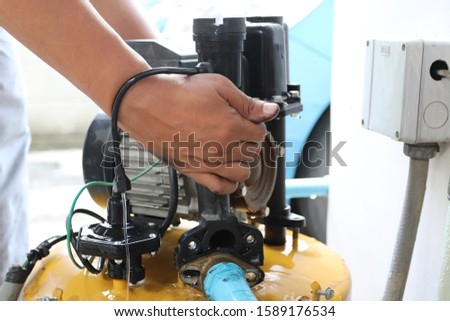 Man fixing house electric water supply system pump, selective focus.