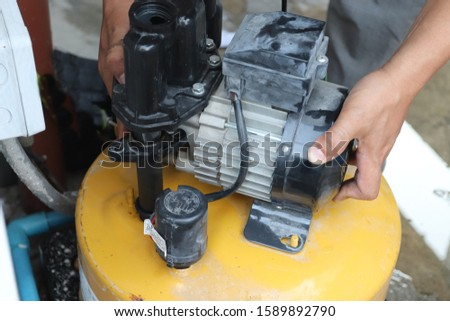 Man fixing house electric water supply system pump, selective focus