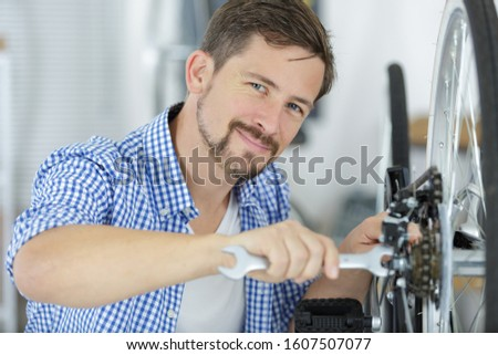 man fixing wheel on a bicycle