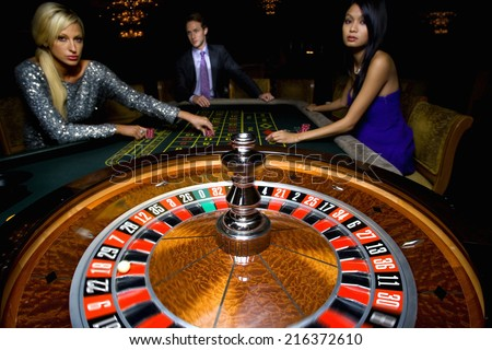 Man flanked by women, gambling at roulette table, portrait