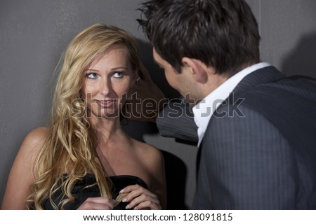 Man flirting with a woman standing at the wall