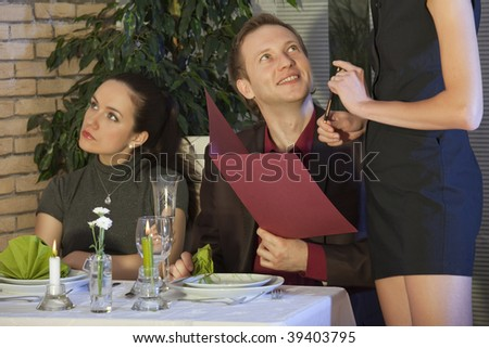 man flirting with waitress, his girlfriend sitting unhappy