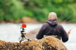 Man Fly fishing on Jacques-Cartier river with go-pro, in Parc national de la Jacques-Cartier, Quebec.
