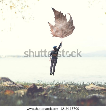 man flying with a leaf, autumnal surreal concept