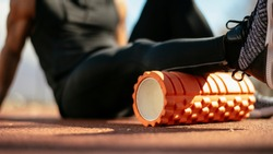 Man foam rolling. Athlete stretches using foam roller.