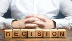 Man folded his hands on a background of blocks with the word Decision. Make the right decision, the answer to the question. Reasoning, weighing results and consequences. Authoritative opinion.