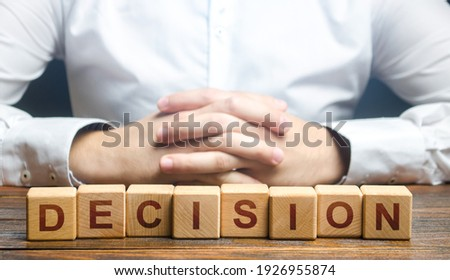 Man folded his hands on a background of blocks with the word Decision. Make the right decision, the answer to the question. Reasoning, weighing results and consequences. Authoritative opinion. Photo stock ©