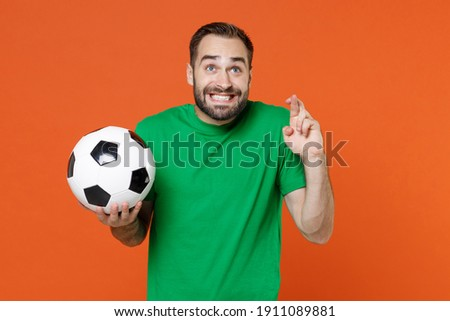 Man football fan in green t-shirt cheer up support favorite team with soccer ball wait for special moment keeping fingers crossed make wish isolated on orange background. People sport leisure concept Foto stock ©