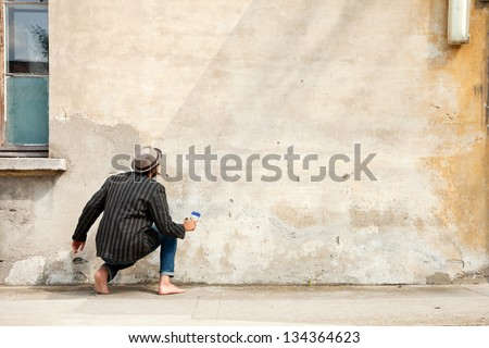 man from behind, writes on a wall