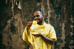 Man from india holds a yellow cup in hands. A man in national Indian clothes drinks tea from a cup