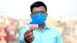 Man from minority group holds I Voted sticker upclose to the camera. selective focus