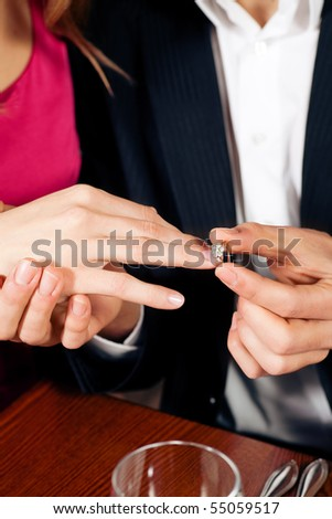 Man gently sticks a diamond ring on the finger of his fiance after a romantic dinner (just hands to be seen)