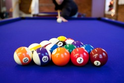 Man gets ready to begin breaking the rack of balls in a billiard game of 8 ball. Very shallow depth of field with sharpest focus on the eight ball.