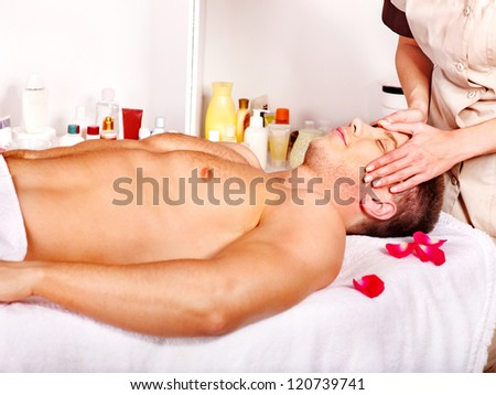 Man getting facial  massage in beauty spa.