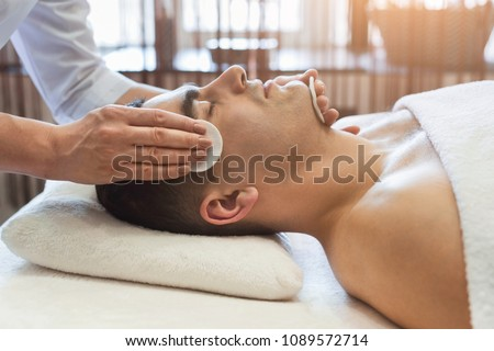 Man getting facial treatment in a beauty SPA salon. Exfoliation, stimulation and hydratation. Aesthetic cosmetology, closeup, copy space #1089572714