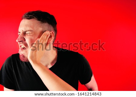 Photo of  Man getting slapped on red background. Unhappy scared man getting slapped standing on red background