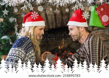 Man gifting woman in front of lit fireplace during Christmas against fir tree forest and snowflakes