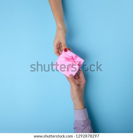 man gives a girl a gift from hand to hand,box wrapped in decorative paper with a bow on blue background, the concept of holidays, love and relationships, top view