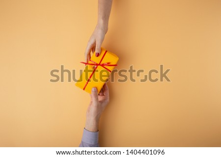 man gives a girl a gift from hand to hand,box wrapped in decorative paper with a bow orange background, the concept of holidays, love and relationships, top view