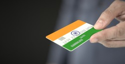 Man gives plastic bank card with printed flag of India. Fictional numbers