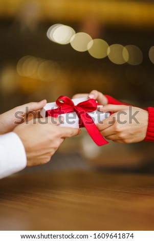 Man gives to his woman a gift box with red ribbon. Hands of man gives surprise gift box for girl. Lovers give each other gifts. Young loving couple celebrating Valentine's Day. Romantic day.