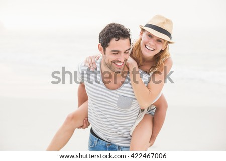 Man giving a piggy back to woman on the beach on a sunny day stock photo