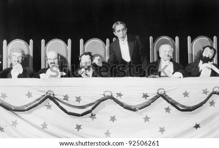 Man giving a speech with five character puppets sitting at the table