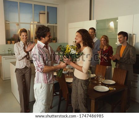 Man giving flowers to girlfriend in kitchen