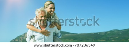 Photo of Man giving his laughing wife a piggy back at the beach on a sunny day