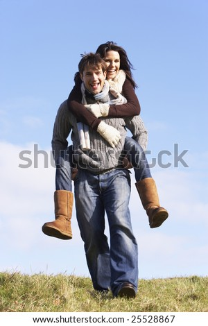 Man Giving His Wife A Piggy Back Ride In Park