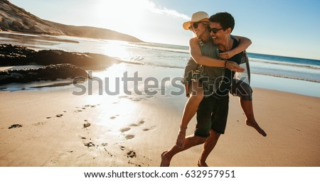 Man giving piggyback ride to girlfriend on beach. Happy young couple having fun on the seashore, enjoying summer holidays. #632957951